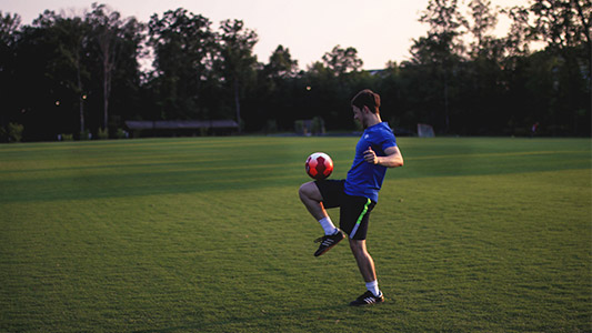 Mann im Trikot auf einem Fußballplatz balanciert einen Ball mit dem Knie