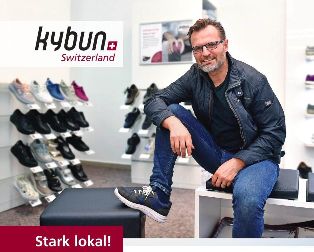 """Ein Mann mittleren Alters mit kybun Schuhen und dem Schriftzug """"Stark lokal!"""