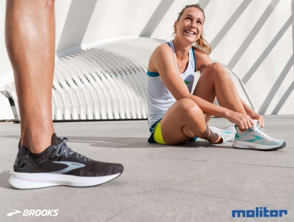 Laufschuhschnürung - Eine Läuferin sitzt und schnürt sich ihre Laufschuhe